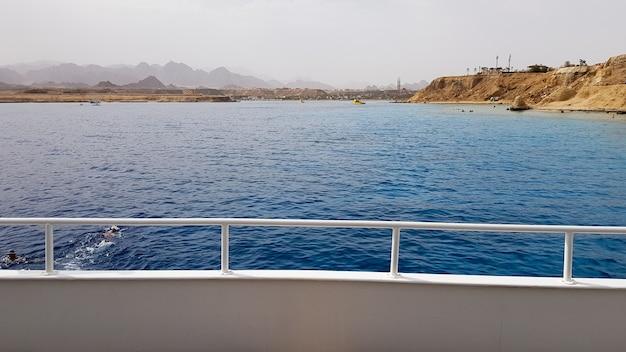 Piękny widok z pokładu statku wycieczkowego na morzu czerwonym w egipcie. egipskie skaliste wybrzeże krajobraz z jachtem. część statku na tle pustyni i morza.