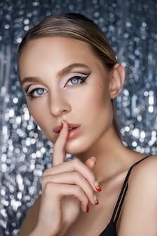 Piękny wieczór makijaż oczu blondynki na błyszczącym tle. close-up portret kobiety, doskonały makijaż oczu, pielęgnacja skóry