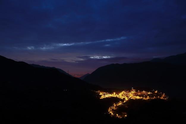 Piękny wieczór na szczycie góry kontemplującej w oddali miasto san bartolome oświetlone dopiero późną nocą.