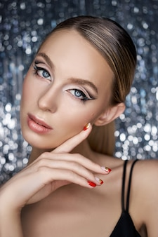 Piękny wieczorowy makijaż oczu blondynki na błyszczącym