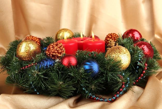 Piękny wieniec bożonarodzeniowy na złotej powierzchni tkaniny
