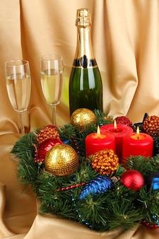 Piękny wieniec bożonarodzeniowy w kompozycji z szampanem na powierzchni tkaniny w kolorze złotym