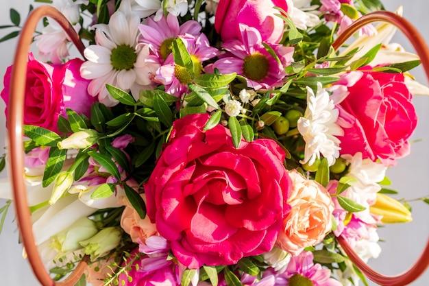 Piękny wiosenny bukiet w papierowym koszyczku z uchwytami. aranżacja z różnymi kwiatami.