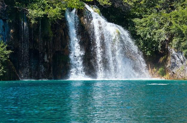 Piękny wodospad i przezroczyste jezioro w kolorze morskiej zieleni w parku narodowym jezior plitwickich (chorwacja)