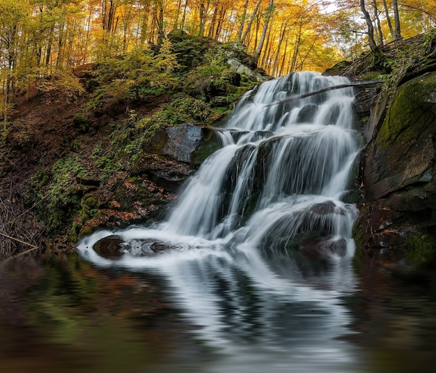 Piękny wodospad jesienią odbicie w jeziorze