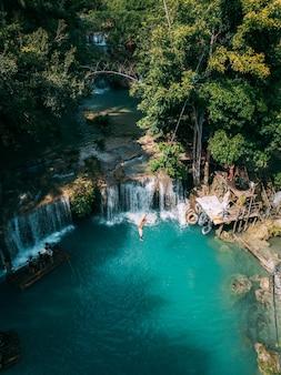 Piękny wodospad spływający do rzeki otoczony zielenią