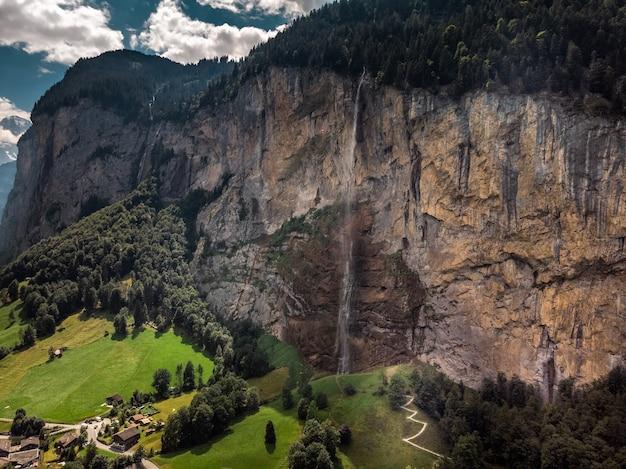 Piękny wodospad staubbachfall spływający po malowniczej dolinie lauterbrunnen i wiosce w kantonie berno