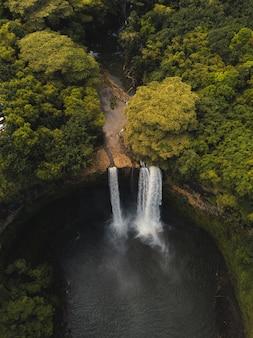 Piękny wodospad wlewający się do rzeki otoczony zielenią