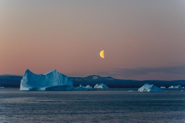 Piękny wschód księżyca na grenlandii. góra lodowa na morzu.