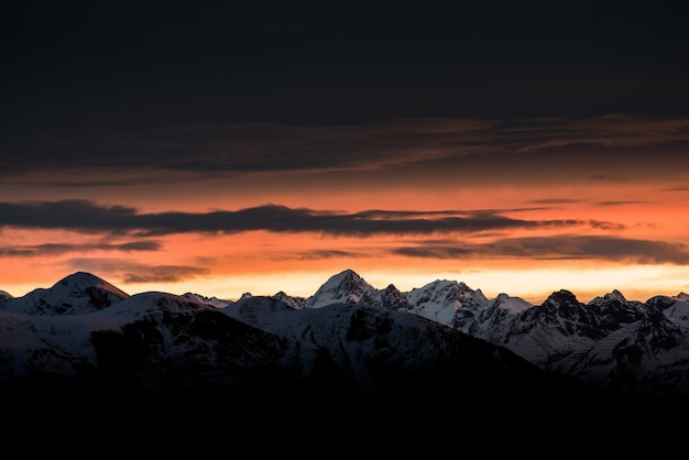 Piękny wschód słońca na horyzoncie z wysokimi górami i zaśnieżonymi wzgórzami i niesamowitym ciemnym niebem