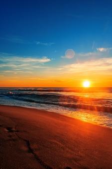 Piękny wschód słońca na plaży pod błękitnym niebem