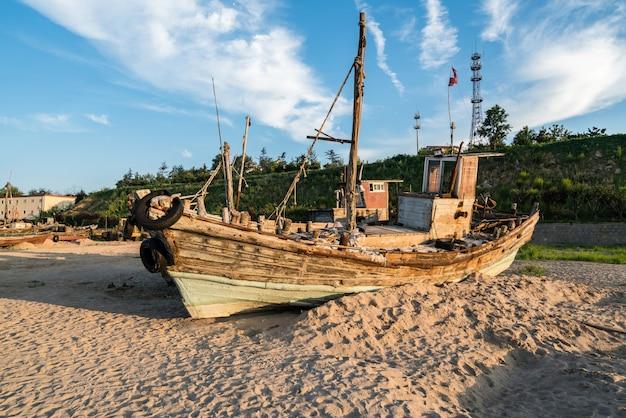 Piękny wschód słońca na starej drewnianej łodzi rybackiej na plaży