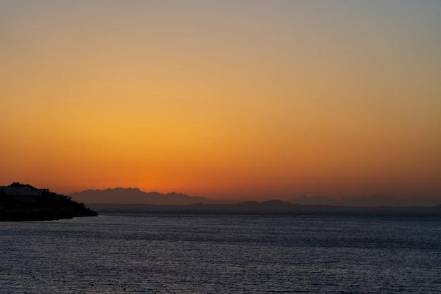 Piękny wschód słońca nad wodą morską w sharm el sheikh, egipt. koncepcja podróży i przyrody. poranne niebo, słońce i morska woda