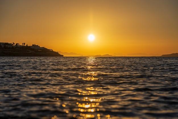 Piękny wschód słońca nad wodą morską w sharm el sheikh, egipt. koncepcja podróży i przyrody. poranne niebo, słońce i woda morska