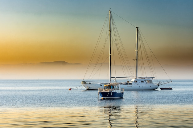 Piękny wschód słońca nad zatoką z jachtem
