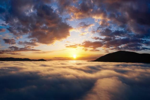 Piękny wschód słońca w górach. malowniczy krajobraz z dramatycznym niebem nad grubymi chmurami w górskiej dolinie. widok z lotu ptaka.