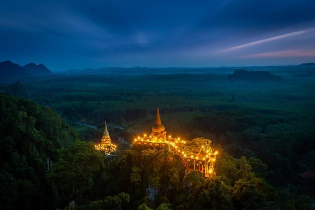 Piękny wschód słońca z pagodą na szczycie skały i drzewa z mgłą w parku khao na nai luang dharma, prowincja surat thani, tajlandia
