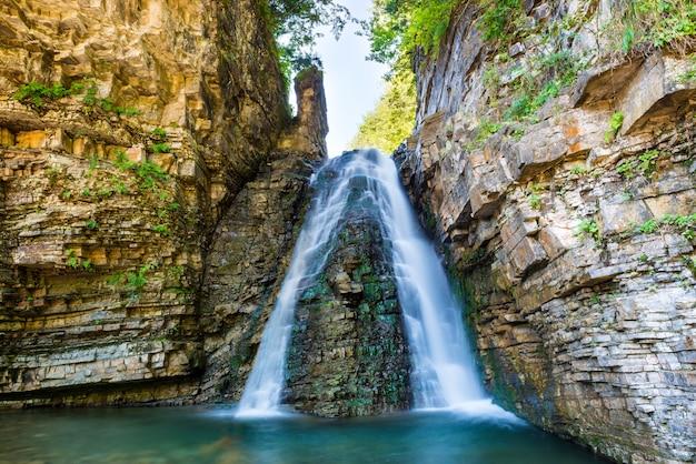 Piękny wysoki wodospad w zielonym lesie