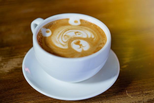 Piękny wzór w postaci niedźwiedzia w białej filiżance z latte wykonaną w restauracji.