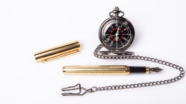 Piękny zabytkowy zegarek kieszonkowy i wieczne pióro na białej powierzchni