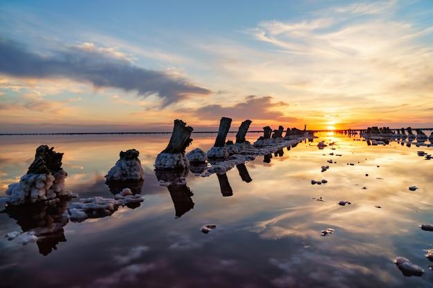 Piękny zachód słońca lub wschód słońca nad słonym jeziorem, konopie drewniane w nagromadzeniu soli po wysuszeniu jeziora