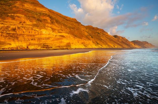 Piękny zachód słońca na ocean beach w nowej zelandii.