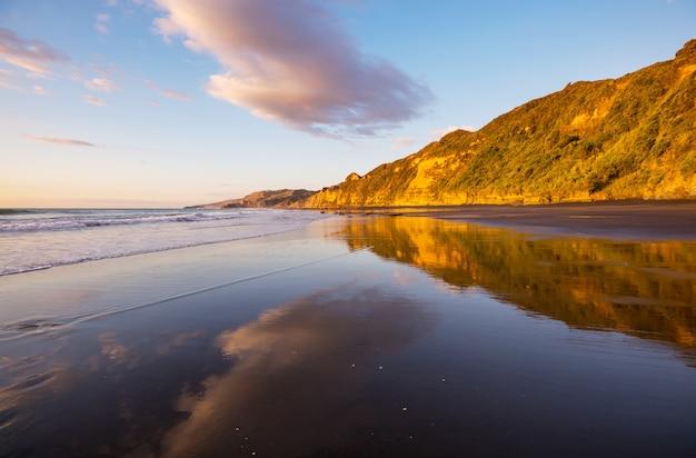 Piękny zachód słońca na plaży ocean beach, nowa zelandia. inspirujące tło naturalne i podróżnicze