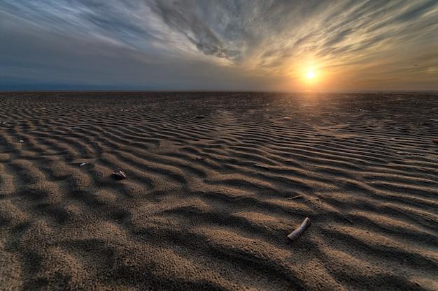 Piękny zachód słońca na plaży stwarzający doskonałą scenerię na wieczorne spacery nad brzegiem