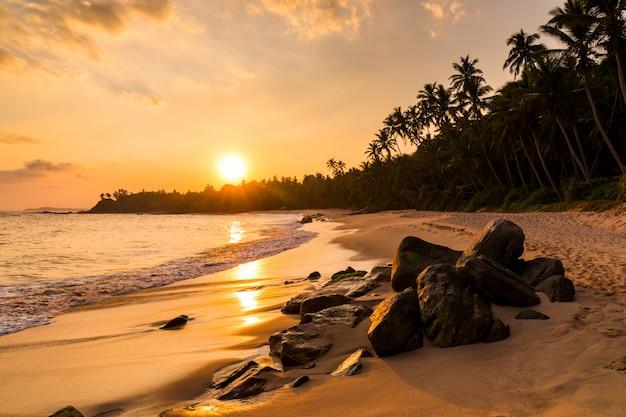 Piękny zachód słońca na plaży z palmami na filipinach