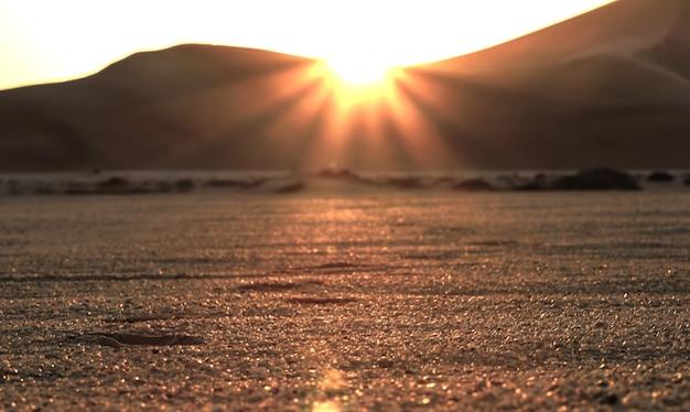 Piękny zachód słońca na pustyni i ślady stóp na piasku?