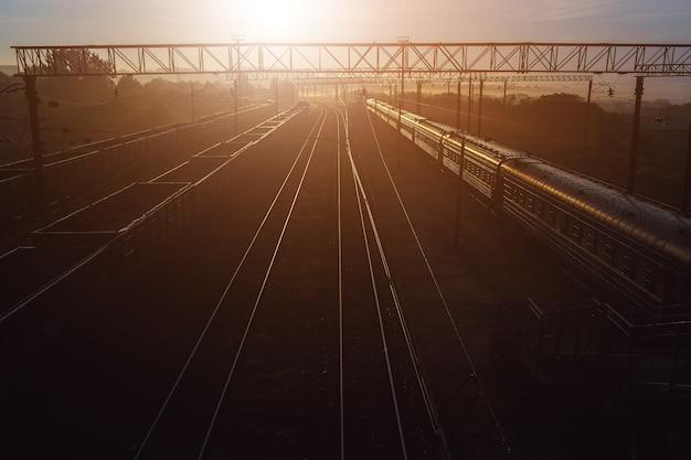Piękny zachód słońca na stacji kolejowej z pociągiem towarowym i pasażerskim.