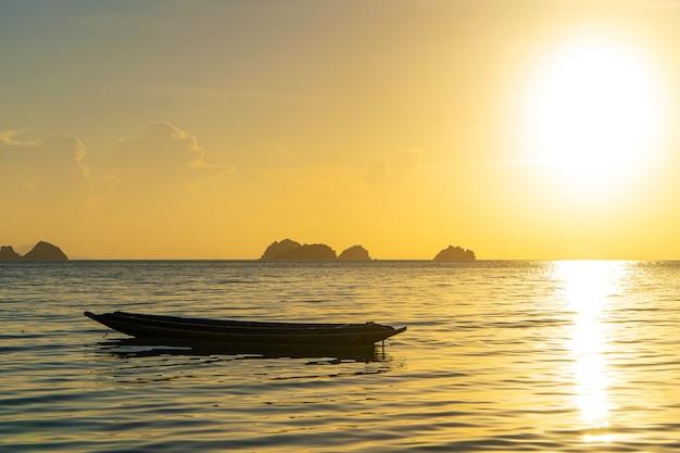 Piękny zachód słońca na wybrzeżu tropikalnej wyspy w tajlandii, sylwetka łodzi na oceanie.