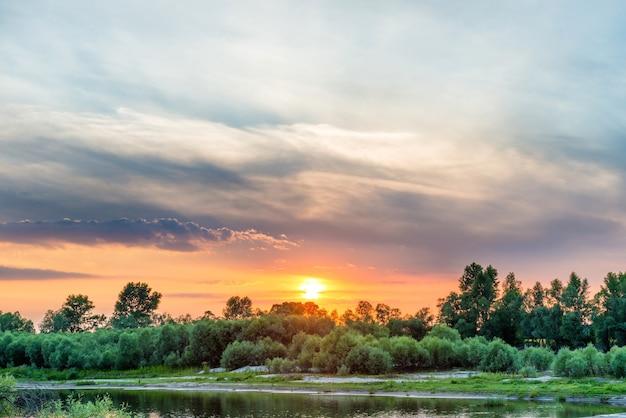 Piękny zachód słońca nad dużą rzeką z zielonym lasem na drugim wybrzeżu i odbiciem nad wodą