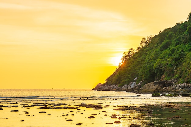 Piękny zachód słońca nad górą wokół plaży, oceanu i skały