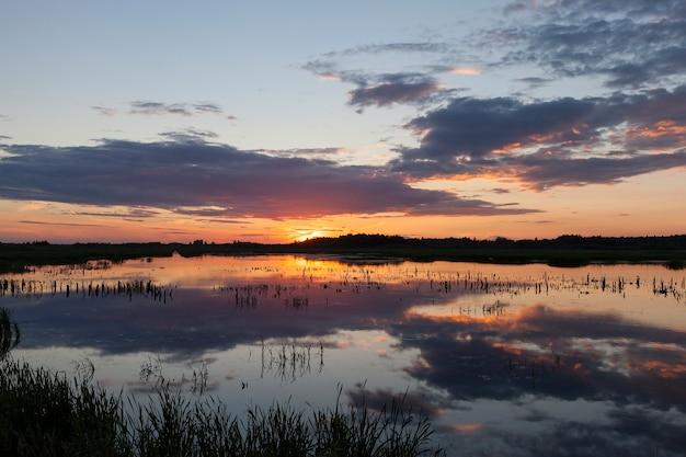 Piękny zachód słońca nad jeziorem w wodzie, w którym odbija się kolorowe niebo, jesienny krajobraz