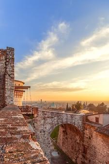 Piękny zachód słońca nad miastem brescia, widok ze starego zamku. lombardia, włochy (zdjęcie pionowe)