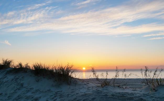 Piękny zachód słońca nad morzem bałtyckim z chmurami i belkami w yantarny, rosja
