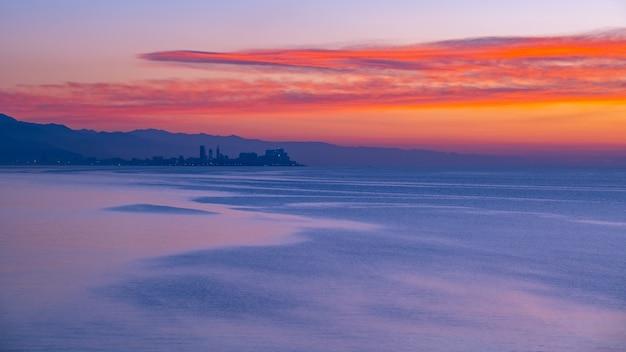 Piękny zachód słońca nad morzem czarnym, w oddali widać miasto batumi. krajobraz