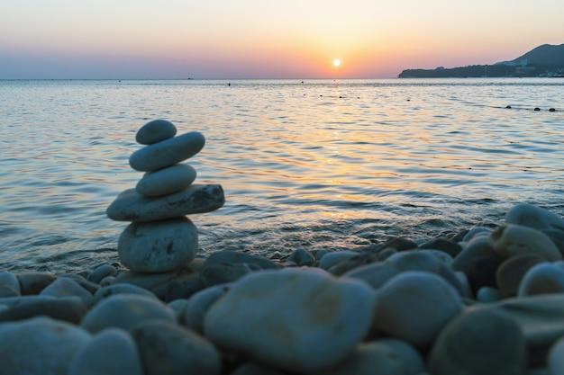 Piękny zachód słońca nad morzem i balansująca piramida z kamieni