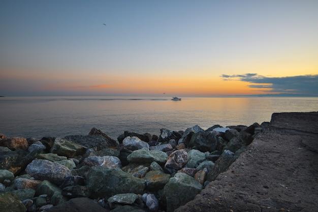 Piękny zachód słońca nad morzem z ramą z kolorowych kamieni