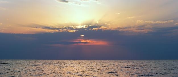 Piękny zachód słońca nad powierzchnią morza. zdjęcie złożone z czterech ujęć.
