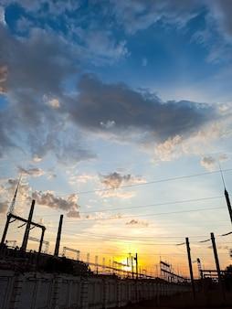 Piękny zachód słońca nad przemysłowym krajobrazem, fabryką, przewodami elektrycznymi, zanieczyszczeniami, na tle pięknej przyrody.