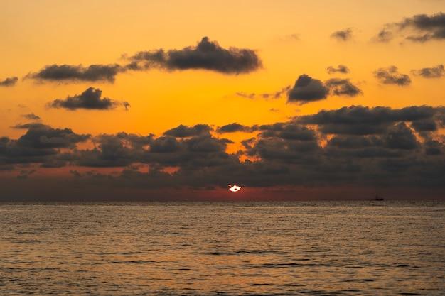 Piękny zachód słońca nad spokojną wodą morską. koncepcja wakacji letnich.