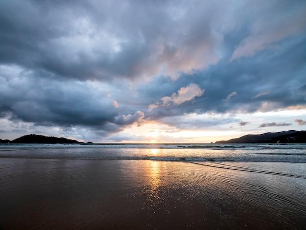 Piękny zachód słońca nad spokojnym morzem z tłem chmury i nieba. zachód słońca nad tropikalną plażą. koncepcja lato natura. szczyt zachód słońca nad morzem z żółtego światła odbijają się w chmurze.