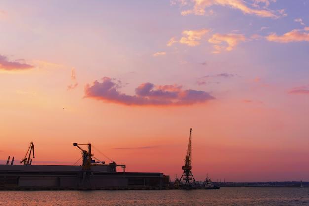 Piękny zachód słońca nad terenem przemysłowym podmiejskiego miasta ze słońcem odbijającym się od wody