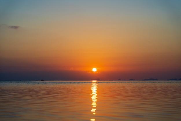 Piękny zachód słońca nad wodą morską na wyspie koh phangan, tajlandia. koncepcja podróży i przyrody. wieczorne niebo, chmury, słońce i woda morska