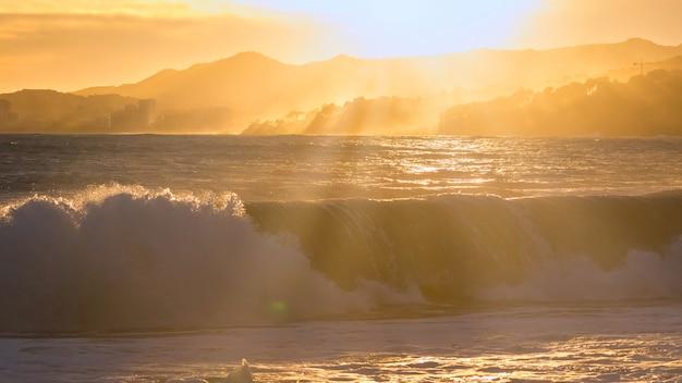 Piękny zachód słońca w hiszpanii z dużymi falami, costa brava