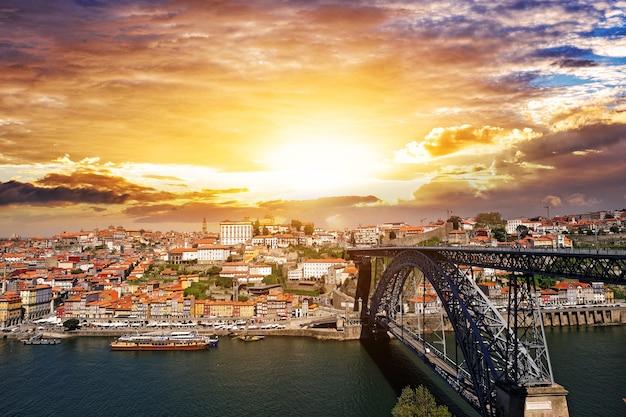 Piękny zachód słońca w porto, portugalia. most dom luis i rzeka douro.