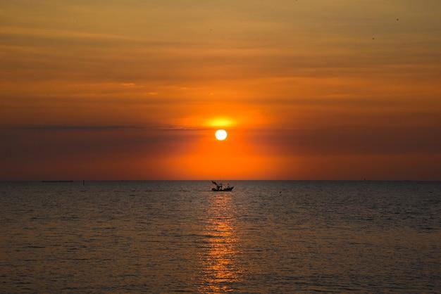 Piękny zachód słońca wieczorem przy plaży bang saen w tajlandii przepłynęła łódź rybacka.