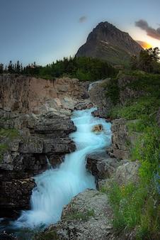 Piękny zachód słońca z wodospadem swiftcurrent falls, glacier national park